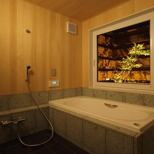 Foto di una stanza da bagno etnica di medie dimensioni con vasca ad angolo, piastrelle grigie, piastrelle di marmo, pareti beige, pavimento in sughero e pavimento nero