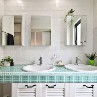 他の地域の北欧スタイルのおしゃれな浴室 (ルーバー扉のキャビネット、白いキャビネット、白い壁、オーバーカウンターシンク、タイルの洗面台、青い洗面カウンター) の写真