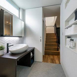 他の地域のコンテンポラリースタイルのおしゃれなバスルーム (浴槽なし) (オープンシェルフ、茶色いキャビネット、白いタイル、磁器タイル、白い壁、磁器タイルの床、ベッセル式洗面器、グレーの床、ブラウンの洗面カウンター) の写真