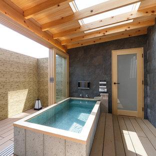 Immagine di una stanza da bagno etnica con vasca freestanding, pareti grigie e pavimento marrone