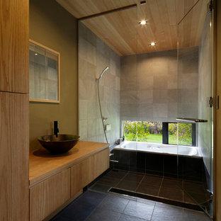 Idéer för funkis badrum, med släta luckor, ett hörnbadkar, en öppen dusch, flerfärgade väggar, ett fristående handfat, träbänkskiva, svart golv och med dusch som är öppen