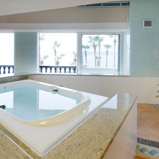 他の地域の地中海スタイルのおしゃれな浴室 (青い壁、トラバーチンの床、オレンジの床、置き型浴槽、オープン型シャワー、オープンシャワー) の写真