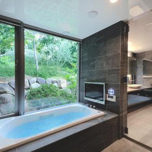 東京都下のモダンスタイルのおしゃれな浴室 (ドロップイン型浴槽、グレーの壁、開き戸のシャワー) の写真