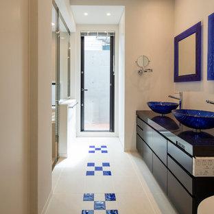中サイズのコンテンポラリースタイルの浴室の写真 (インセット扉のキャビネット、黒いキャビネット、白いタイル、白い壁、セラミックタイルの床、ベッセル式洗面器、クオーツストーンの洗面台、青い床)