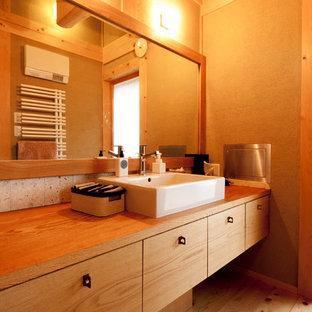 Asiatisches Badezimmer mit flächenbündigen Schrankfronten, hellbraunen Holzschränken, brauner Wandfarbe, braunem Holzboden, Aufsatzwaschbecken, Waschtisch aus Holz, braunem Boden und brauner Waschtischplatte in Sonstige