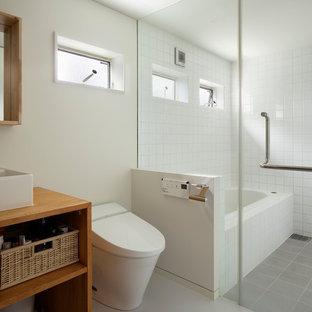 横浜の小さいコンテンポラリースタイルのおしゃれなマスターバスルーム (中間色木目調キャビネット、アンダーマウント型浴槽、一体型トイレ、白い壁、磁器タイルの床、ベッセル式洗面器、グレーの床) の写真
