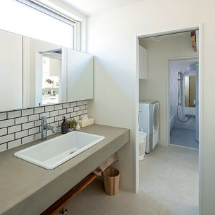 他の地域のコンテンポラリースタイルのおしゃれな浴室 (オープンシェルフ、白いタイル、サブウェイタイル、白い壁、オーバーカウンターシンク、コンクリートの洗面台、グレーの床) の写真