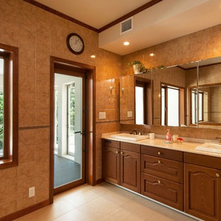 他の地域の地中海スタイルのおしゃれな浴室 (落し込みパネル扉のキャビネット、中間色木目調キャビネット、茶色いタイル、茶色い壁、オーバーカウンターシンク、ベージュの床) の写真