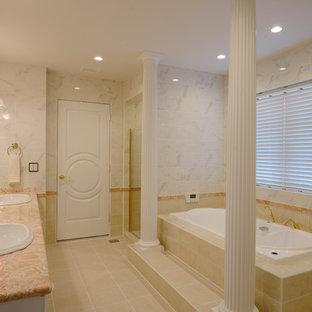 他の地域のトラディショナルスタイルのおしゃれな浴室 (白いキャビネット、コーナー型浴槽、グレーのタイル、白いタイル、グレーの壁、オーバーカウンターシンク、ベージュの床) の写真
