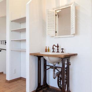 他の地域のカントリー風おしゃれな浴室 (白い壁、無垢フローリング、木製洗面台、茶色い床、ブラウンの洗面カウンター) の写真