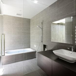 他の地域のモダンスタイルのおしゃれな浴室 (インセット扉のキャビネット、茶色いキャビネット、ドロップイン型浴槽、グレーのタイル、磁器タイル、ベッセル式洗面器、クオーツストーンの洗面台、黒い洗面カウンター、グレーの床) の写真