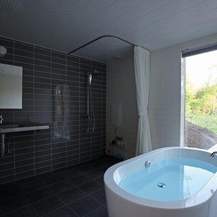 モダンスタイルのおしゃれなマスターバスルーム (グレーのタイル、置き型浴槽、オープン型シャワー、マルチカラーの壁、黒い床、シャワーカーテン) の写真