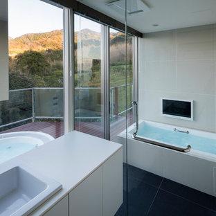 他の地域のモダンスタイルのおしゃれな浴室 (フラットパネル扉のキャビネット、白いキャビネット、ドロップイン型浴槽、ベージュのタイル、磁器タイル、白い壁、磁器タイルの床、オーバーカウンターシンク、人工大理石カウンター、グレーの床、白い洗面カウンター) の写真