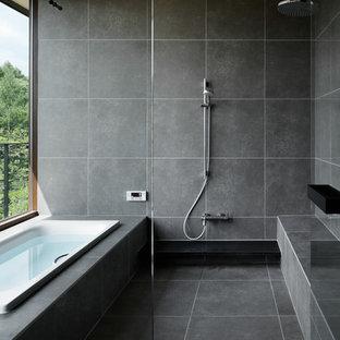 他の地域のモダンスタイルのおしゃれな浴室 (コーナー型浴槽、グレーの壁、グレーの床、オープンシャワー) の写真