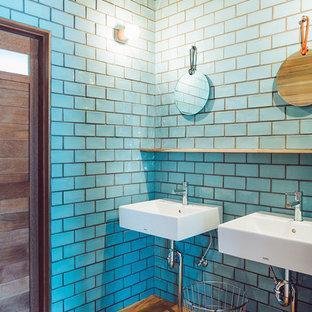 他の地域のコンテンポラリースタイルのおしゃれな浴室 (青いタイル、サブウェイタイル、壁付け型シンク、青い壁、無垢フローリング) の写真