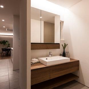 Неиссякаемый источник вдохновения для домашнего уюта: туалет в стиле модернизм с плоскими фасадами, фасадами цвета дерева среднего тона, белыми стенами, настольной раковиной, столешницей из дерева, серым полом и коричневой столешницей