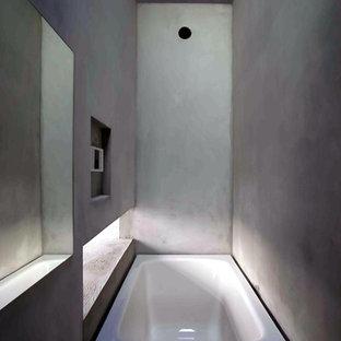 Modelo de cuarto de baño principal, minimalista, de tamaño medio, sin sin inodoro, con bañera empotrada, baldosas y/o azulejos naranja, paredes grises, suelo de cemento, suelo gris y ducha abierta