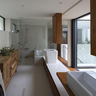他の地域の広いコンテンポラリースタイルのおしゃれなマスターバスルーム (フラットパネル扉のキャビネット、中間色木目調キャビネット、ドロップイン型浴槽、シャワー付き浴槽、グレーのタイル、白い壁、磁器タイルの床、ベッセル式洗面器、グレーの床、オープンシャワー、白い洗面カウンター、洗面台1つ、フローティング洗面台) の写真