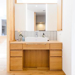 Ejemplo de cuarto de baño de estilo zen con armarios con paneles lisos, puertas de armario de madera oscura, paredes blancas, suelo de madera clara, lavabo sobreencimera, encimera de madera, suelo marrón y encimeras marrones