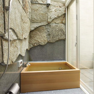 This is an example of a contemporary bathroom in Osaka with gray tile, multi-coloured walls and a japanese tub.