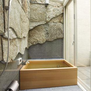 Foto di una stanza da bagno design con piastrelle grigie, pareti multicolore e vasca giapponese