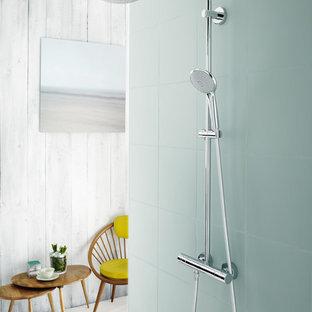 Immagine di una stanza da bagno scandinava con doccia aperta, piastrelle di vetro e pareti grigie