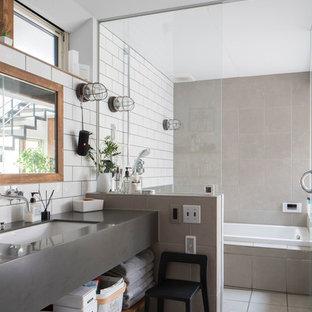 札幌のコンテンポラリースタイルのおしゃれな浴室 (ドロップイン型浴槽、グレーのタイル、白いタイル、白い壁、アンダーカウンター洗面器、グレーの床、グレーの洗面カウンター) の写真