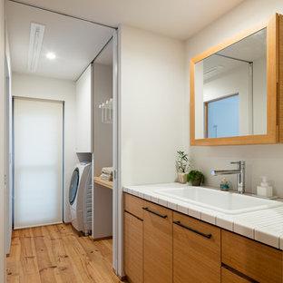 他の地域のビーチスタイルのおしゃれな浴室 (フラットパネル扉のキャビネット、中間色木目調キャビネット、白い壁、オーバーカウンターシンク、タイルの洗面台、茶色い床、淡色無垢フローリング) の写真