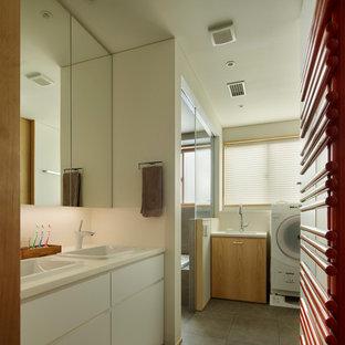 Modelo de cuarto de baño de estilo zen, de tamaño medio, con armarios con paneles lisos, puertas de armario blancas, paredes blancas, suelo de baldosas de cerámica, lavabo encastrado, encimera de acrílico, suelo gris, encimeras blancas, ducha a ras de suelo y ducha con puerta con bisagras