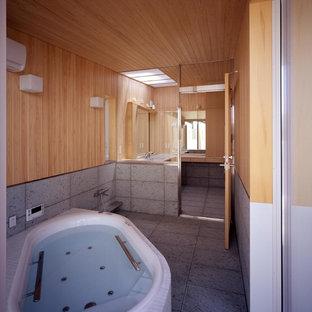 Foto di una stanza da bagno padronale etnica con ante lisce, ante beige, vasca sottopiano, piastrelle verdi, lastra di pietra, lavabo sottopiano, top in superficie solida e pavimento verde