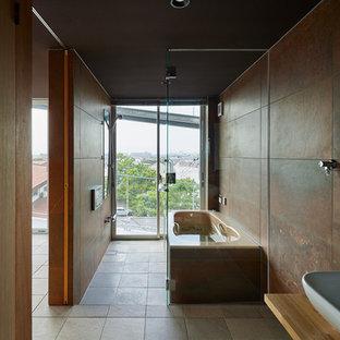 他の地域のインダストリアルスタイルのおしゃれな浴室 (置き型浴槽、茶色い壁、グレーの床) の写真