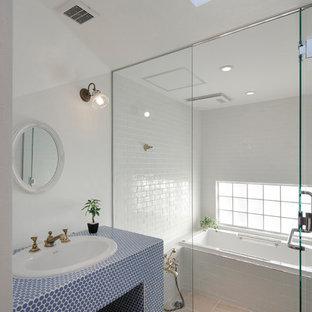 東京23区の地中海スタイルのおしゃれなマスターバスルーム (オープンシェルフ、青いキャビネット、ドロップイン型浴槽、白いタイル、白い壁、セラミックタイルの床、オーバーカウンターシンク、ベージュの床、開き戸のシャワー、青い洗面カウンター) の写真