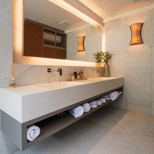 Cette image montre une grande salle de bain principale design avec un placard sans porte, des portes de placard beiges, un carrelage beige, des carreaux de porcelaine, un mur gris, un sol en carrelage de porcelaine, un lavabo intégré, un plan de toilette en terrazzo, un sol gris et un plan de toilette beige.