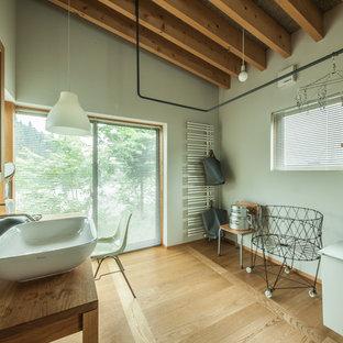 他の地域のアジアンスタイルのおしゃれな浴室 (緑の壁、無垢フローリング、ベッセル式洗面器、木製洗面台、茶色い床) の写真