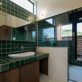 他の地域のアジアンスタイルのおしゃれな浴室 (茶色いキャビネット、緑のタイル、緑の壁、磁器タイルの床、ベージュの床、開き戸のシャワー、ベッセル式洗面器) の写真