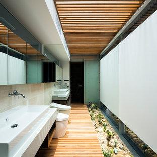 Esempio di una stanza da bagno minimal con nessun'anta, WC monopezzo, pareti bianche, pavimento in legno massello medio, lavabo rettangolare, ante nere, piastrelle beige, pavimento marrone e top bianco