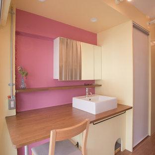 東京23区のアジアンスタイルのおしゃれな浴室 (ガラス扉のキャビネット、無垢フローリング、ベッセル式洗面器、木製洗面台、ピンクの壁) の写真