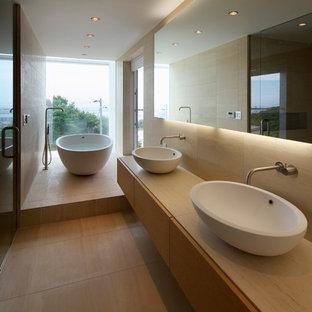 Foto de cuarto de baño principal, moderno, con armarios con paneles lisos, puertas de armario de madera clara, bañera exenta, paredes beige, lavabo sobreencimera, encimera de madera y encimeras beige