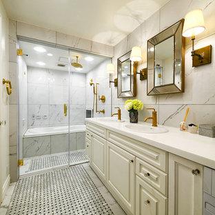東京23区のトラディショナルスタイルのおしゃれな浴室 (レイズドパネル扉のキャビネット、ベージュのキャビネット、ドロップイン型浴槽、白いタイル、オーバーカウンターシンク、グレーの床、白い洗面カウンター) の写真