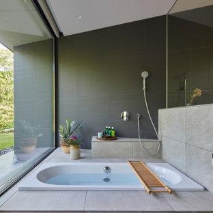 他の地域のコンテンポラリースタイルのおしゃれなマスターバスルーム (ドロップイン型浴槽、グレーのタイル、グレーの床、三角天井、造り付け洗面台、パネル壁、磁器タイル、洗い場付きシャワー) の写真