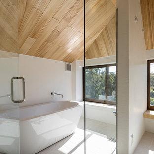 東京都下の中くらいのコンテンポラリースタイルのおしゃれなマスターバスルーム (ガラス扉のキャビネット、白いキャビネット、置き型浴槽、セラミックタイルの床、木製洗面台、白い床) の写真