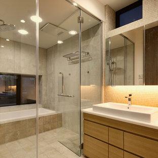 東京23区の広いモダンスタイルのおしゃれなマスターバスルーム (家具調キャビネット、淡色木目調キャビネット、ドロップイン型浴槽、オープン型シャワー、ベージュのタイル、モザイクタイル、グレーの壁、磁器タイルの床、オーバーカウンターシンク、人工大理石カウンター、ベージュの床、オープンシャワー、白い洗面カウンター) の写真