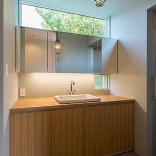 他の地域のモダンスタイルの浴室・バスルームの画像 (フラットパネル扉のキャビネット、中間色木目調キャビネット、白い壁、木製洗面台、グレーの床、ブラウンの洗面カウンター)
