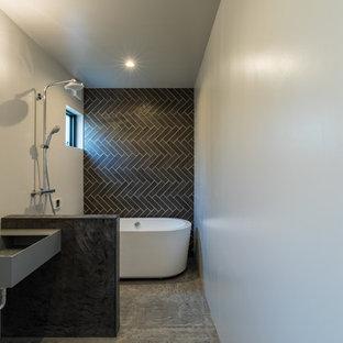 他の地域のコンテンポラリースタイルのおしゃれな浴室 (置き型浴槽、黒いタイル、白い壁、コンクリートの床、コンクリートの洗面台、グレーの床) の写真