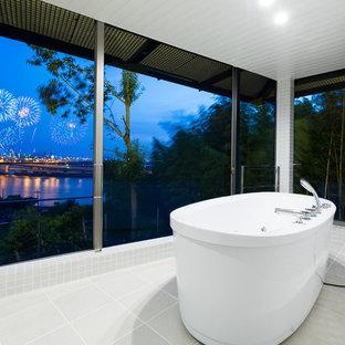 他の地域のモダンスタイルのおしゃれな浴室 (置き型浴槽、グレーのタイル、グレーの壁) の写真