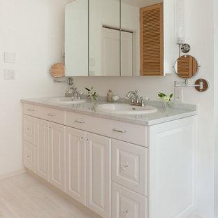 Diseño de cuarto de baño de tamaño medio con armarios tipo vitrina, baldosas y/o azulejos con efecto espejo, paredes blancas, suelo de madera clara, lavabo encastrado y encimera de cuarzo compacto