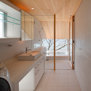 Example of a minimalist white tile drop-in bathtub design in Other with flat-panel cabinets, white cabinets, white walls and a vessel sink