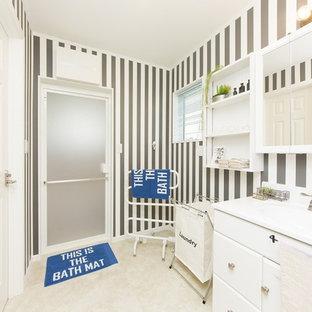 他の地域のコンテンポラリースタイルのおしゃれな浴室 (フラットパネル扉のキャビネット、白いキャビネット、マルチカラーの壁、一体型シンク、ベージュの床) の写真