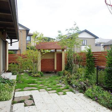草花が彩る東屋のある庭の家