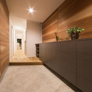 Idee per un ingresso o corridoio minimalista con pareti marroni, pavimento in cemento, una porta scorrevole e pavimento grigio